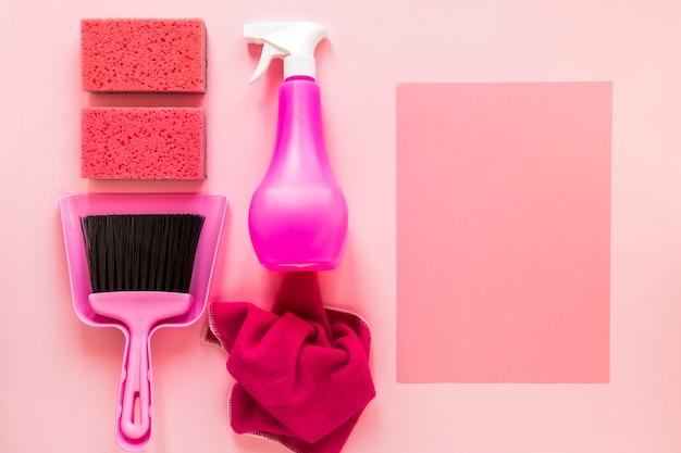 Disposizione vista dall'alto con prodotti per la pulizia su sfondo rosa