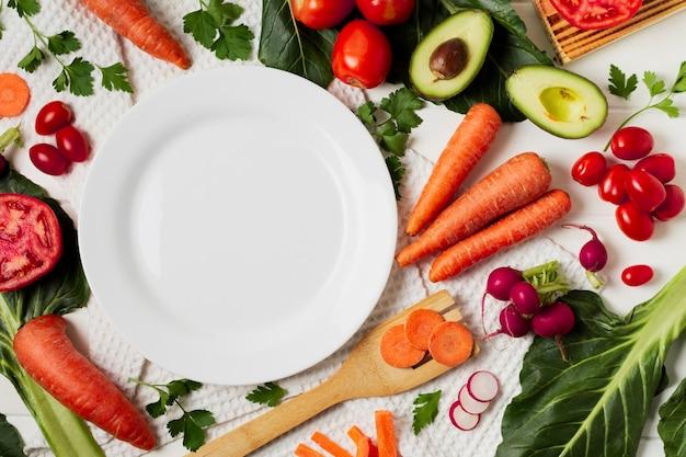 Disposizione vista dall'alto con verdure e piastra vuota