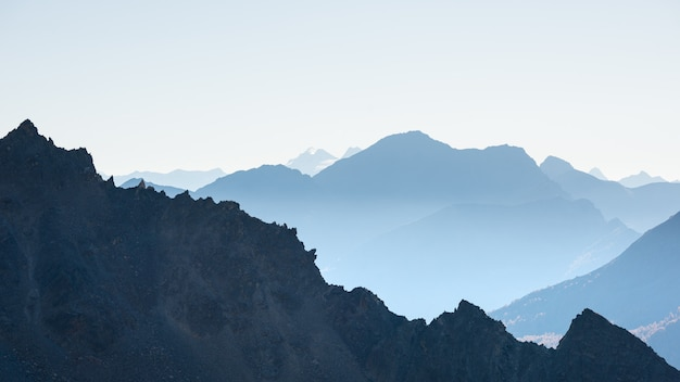 Distante silhouette di montagna con cielo sereno e luce soffusa.