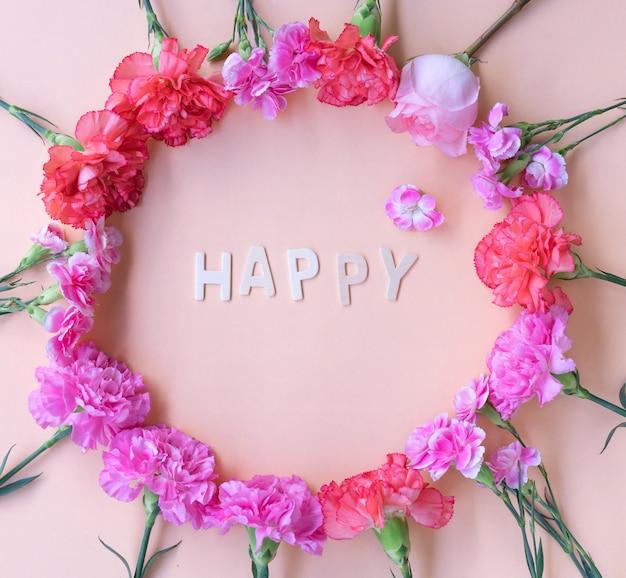 Distesa minima piatta ispirazione felice parola in legno con cornice di fiori freschi