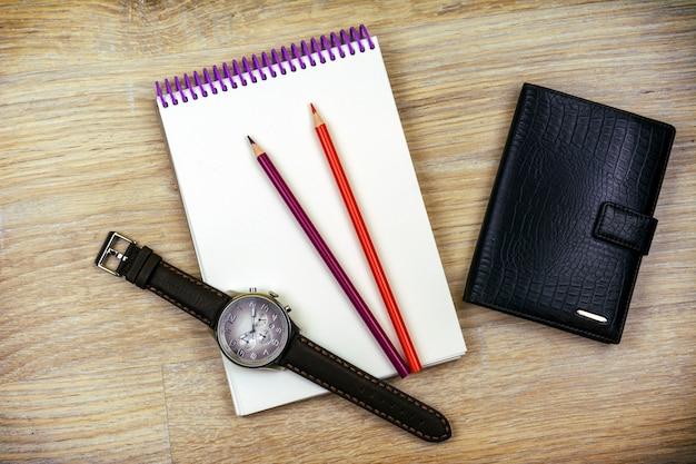 Distesi. l'orologio da polso da uomo, il blocchetto per appunti, due matite e un portafoglio da uomo si trovano sulla trama del legno