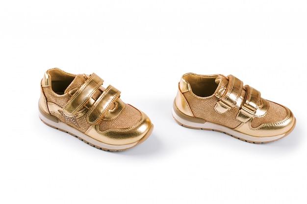 Distesi. le scarpe sportive per bambini d'oro isolate su bianco