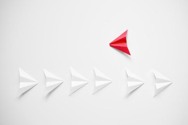 Distinguersi concetto. aeroplano di carta rosso che si staglia dalla linea di bianchi e che cerca di essere contro tutti.