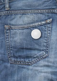 Distintivo in bianco su uno sfondo di tasca blu denim
