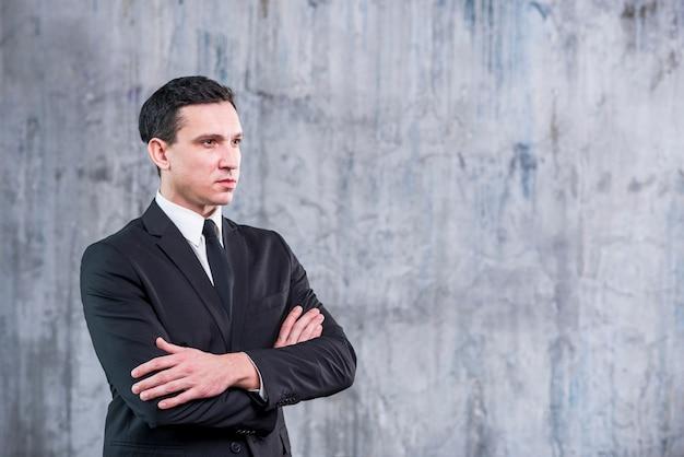 Distogliere lo sguardo dell'uomo d'affari con le braccia attraversate