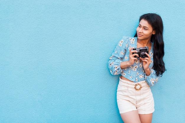 Distogliere lo sguardo donna e retro macchina fotografica con lo spazio della copia