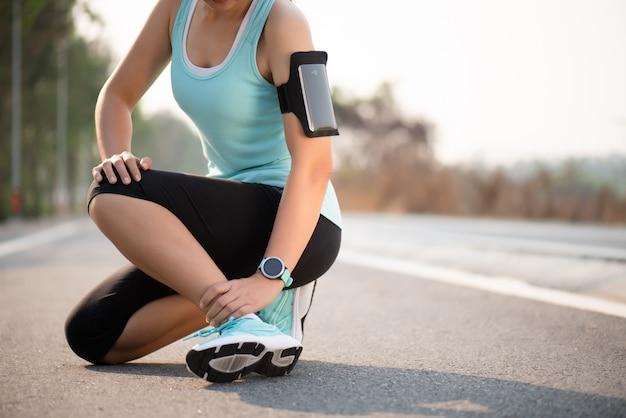 Distorsione alla caviglia. donna che soffre di un infortunio alla caviglia durante l'esercizio e la corsa