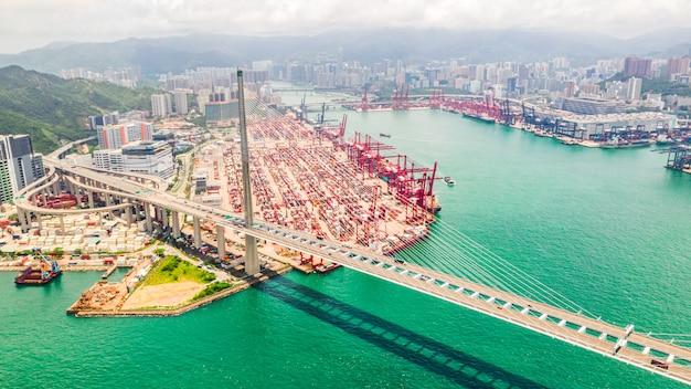 Distretto industriale del porto di hong kong con il contenitore di carico e il ponte degli stonecutters.