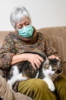 Disturbo sociale del coronavirus a causa dell'epidemia di pandemia. donna anziana con maschera protettiva, rimanere a casa accarezzando il suo gatto.