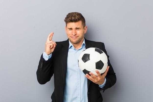 Dita dell'incrocio del giovane istruttore di calcio per avere fortuna