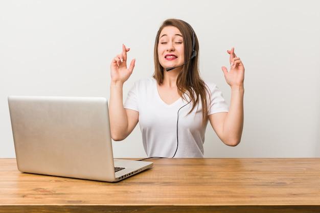 Dita dell'incrocio della giovane donna di telemarketer per avere fortuna