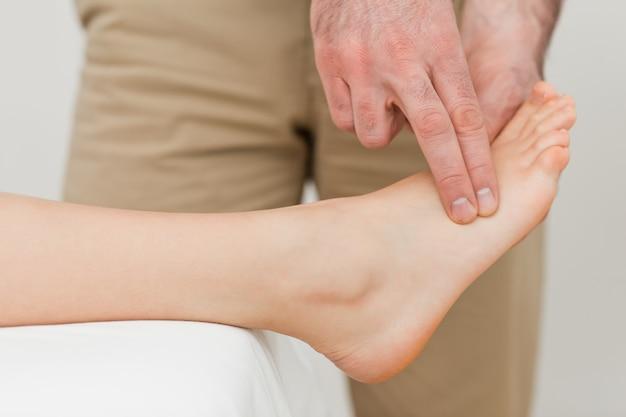 Dita di un fisioterapista che preme su un piede