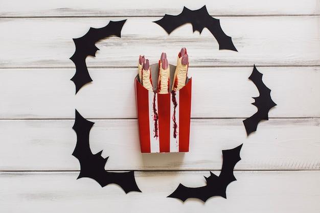 Dita tagliate in scatola circondata da pipistrelli