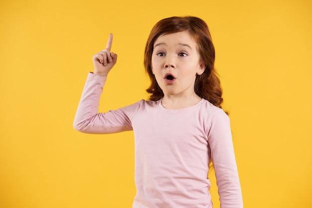 Dito alzato ragazza dai capelli rossi, venendo con l'idea. eureka.