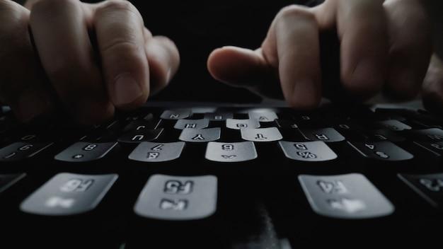 Dito del primo piano soft-focus che scrive sulla tastiera.
