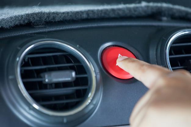 Dito della donna che preme il bottone di emergenza sul cruscotto dell'automobile nel tono di colore d'annata