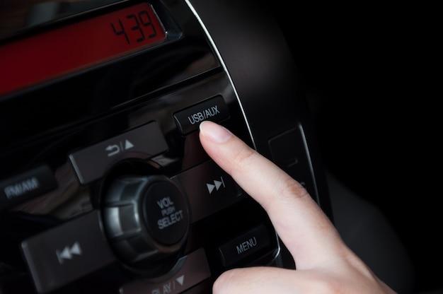 Dito della donna che preme il dettaglio del pulsante (usb aux) sul cruscotto di un'auto, interni dell'auto