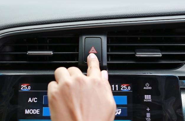 Dito donna premendo il pulsante di emergenza sul cruscotto dell'automobile