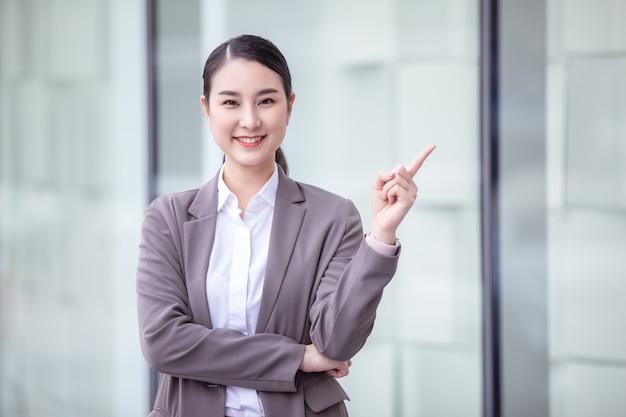 Dito puntato asiatico sorridente della donna di affari