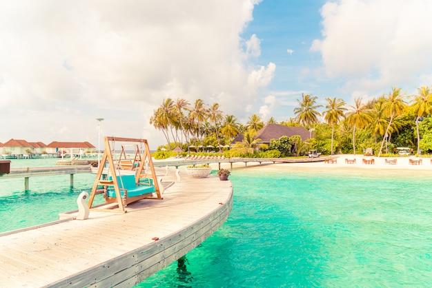 Divano altalena con resort tropicale delle maldive e mare
