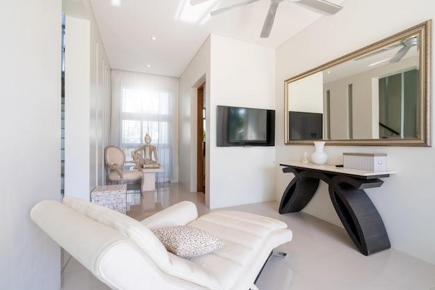Divano bianco, ventilatore a soffitto e televisione nel soggiorno della villa con piscina, casa. casa, condominio e appartamento