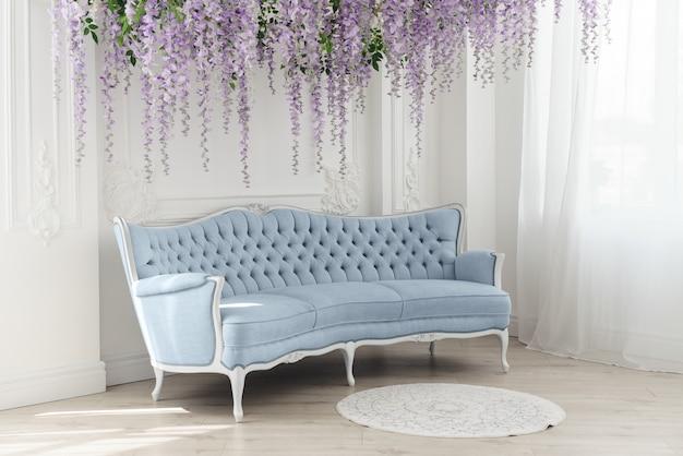 Divano francese blu nella stanza bianca con fiori viola appesi decorativi