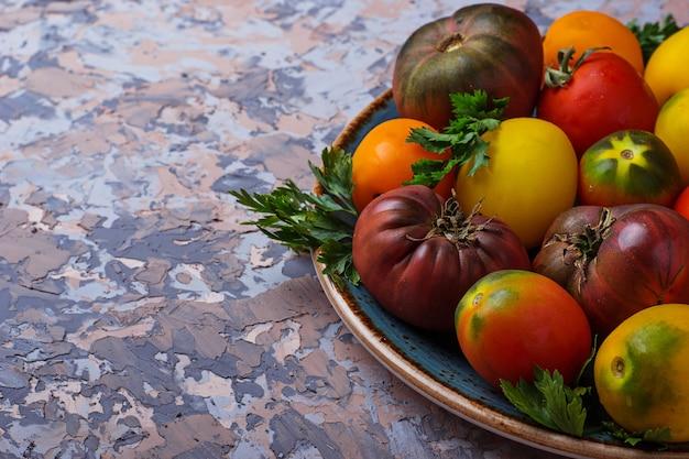 Diversa specie di pomodoro su sfondo concreto. messa a fuoco selettiva