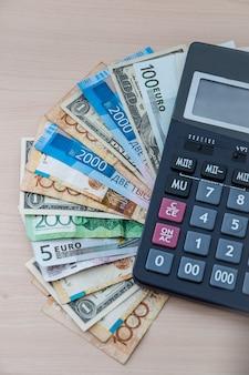 Diverse banconote di diverse virtù sono fan sulla tua scrivania con una calcolatrice