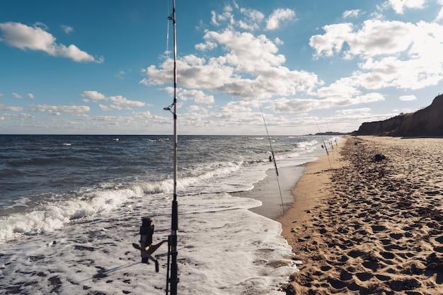 Diverse canne da pesca in fila sulla spiaggia