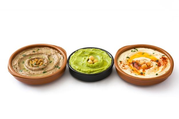 Diverse ciotole di hummus hummus di ceci, hummus di avocado e hummus di lenticchie isolato su bianco