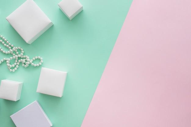 Diverse dimensioni di scatole e collana di perle su sfondo colorato