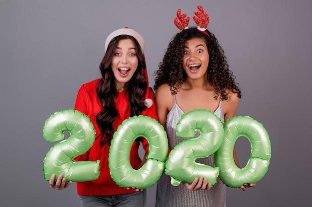 Diverse donne con i palloni del nuovo anno 2020 che portano il cappello di natale isolato sopra gray