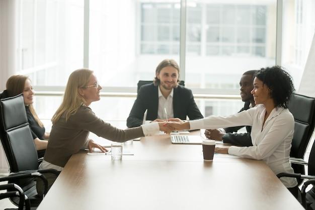 Diverse donne di affari sorridenti che agitano le mani che accolgono alla riunione di gruppo multirazziale
