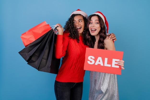 Diverse donne felici con i sacchetti della spesa variopinti e il segno rosso di vendita del copyspace isolati sopra il blu
