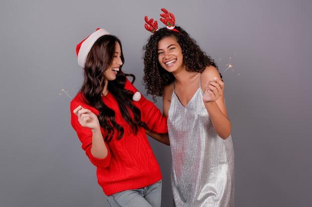 Diverse donne felici con le stelle filanti scintillanti che portano il cappello di natale isolato sopra grey