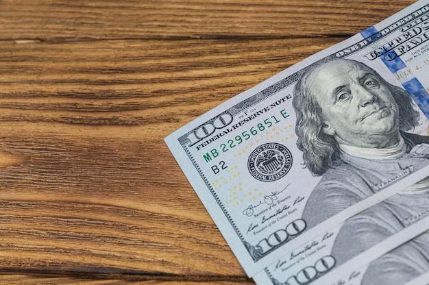 Diverse nuove banconote da cento dollari giacciono diagonalmente su un tavolo di legno strutturato. parte visibile delle bollette.