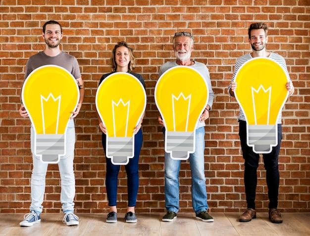 Diverse persone che tengono le icone della lampadina