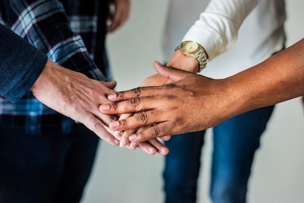 Diverse persone che uniscono le mani al lavoro di squadra