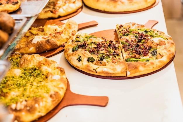 Diverse piccole pizze in stile italiano in una bancarella di strada.