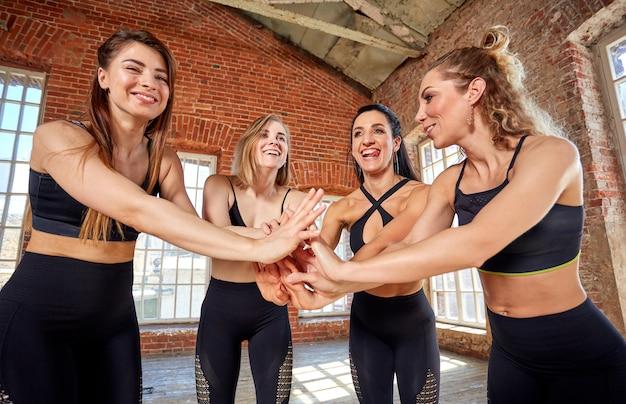 Diverse ragazze divertenti insieme in cerchio su stuoie di gomma che indossano il gesto sorridente di saluto di yoga di manifestazione degli abiti sportivi, esaminando macchina fotografica, cima sopra la vista. namaste, simbolo di saluto e apprezzamento