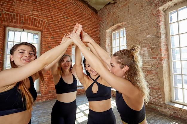 Diverse ragazze divertenti insieme in cerchio su tappetini in gomma che indossano abbigliamento sportivo