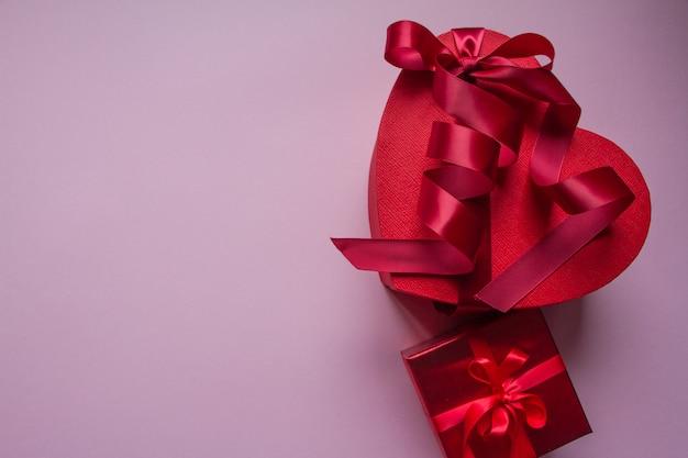 Diverse scatole regalo rosso di diverse forme con nastro rosso