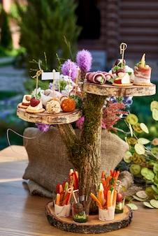 Diverse tartine con salmone affumicato, cetrioli, pomodori, formaggio, carne. tavolo per la colazione a buffet con una varietà di snack. tavolo a buffet con snack, frutta, canape, dolci e stuzzichini.