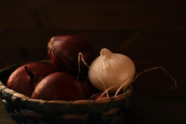 Diverse teste di cipolla rossa spagnola e una lampadina bianca sono piegate in un cesto di vimini. sfondo marrone scuro