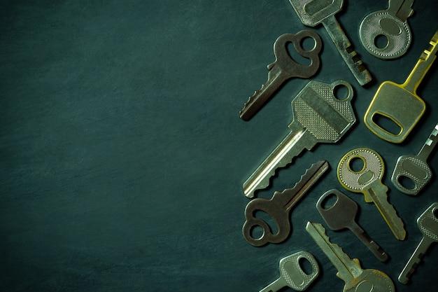 Diverse varietà di chiavi vintage sono posizionate sul pavimento di legno nero sullo sfondo di oscurità
