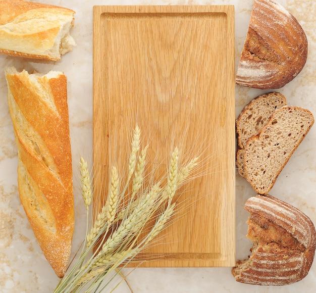 Diverse varietà di pane e spighe di grano su tavola di legno