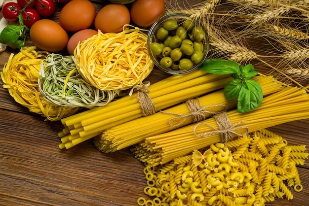 Diverse varietà di pasta, bukatini e fettuccine e girandole sul tavolo con basilico e olive, anche con uova di gallina, pomodori