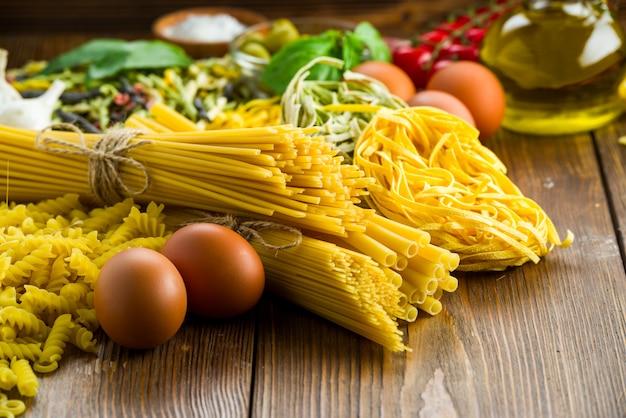 Diverse varietà di pasta sul tavolo con basilico e olive, anche con uova di gallina