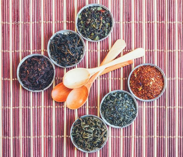 Diverse varietà di tè e cucchiaio di legno su una stuoia di bambù.