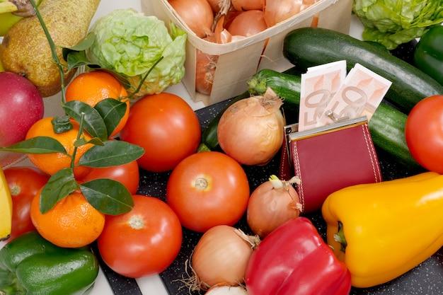 Diverse verdure e frutta di stagione con contanti